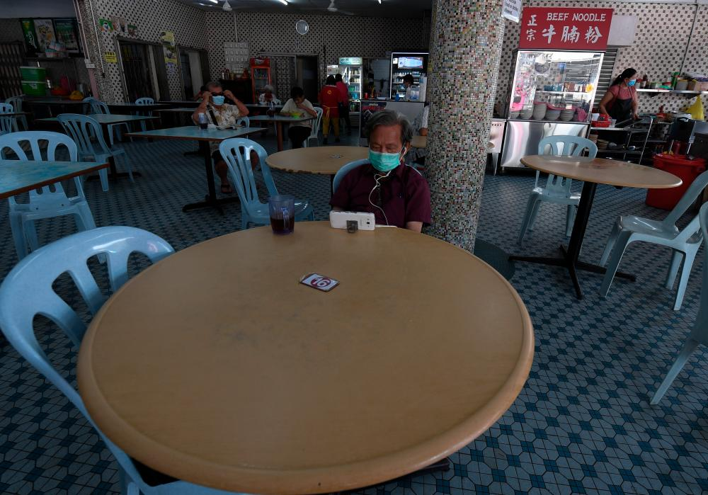 Restaurant customers are seen following the rules of the CMCO after several business and transport sectors were allowed to operate beginning today. - Bernama