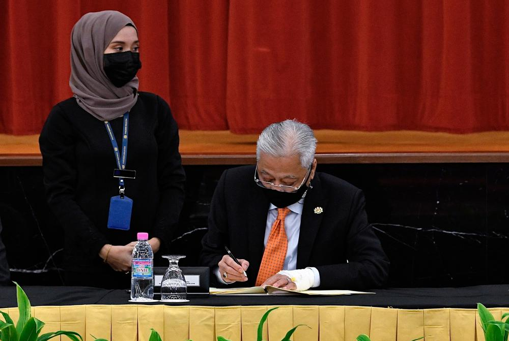 Prime Minister Datuk Seri Ismail Sabri Yaakob signed a document while attending the Signing Ceremony of the Memorandum of Understanding on Transformation and Political Stability between the Federal Government and Pakatan Harapan at the Parliament Building on Sept 13.BERNAMApix