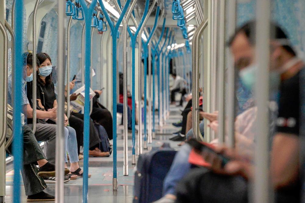 Passengers with face masks maintain social distancing while travelling on the MRT during the MRCO period. — Sunpix by Adib Rawi Yahya