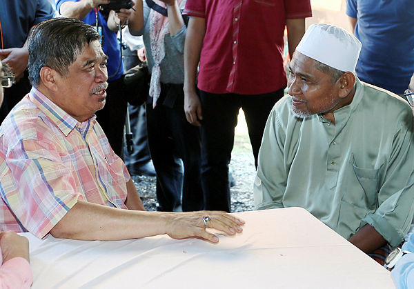 Minister of Defence Mohamad Sabu speaks with fallen firefighter Muhammad Adib's father, Mohd Kassim Abdul Hamid, while visiting the family in Kampung Tebengau, Kuala Kedah. — BBXpress