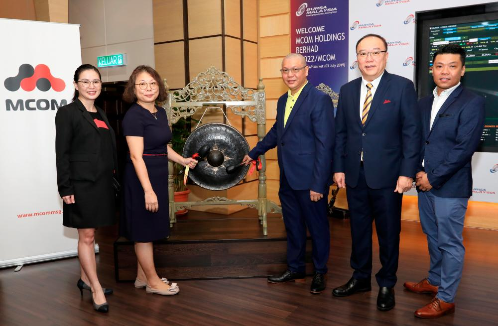Executive director Chew Lee Poh (second from left) and Ho (centre) hitting the gong at the listing ceremony this morning.