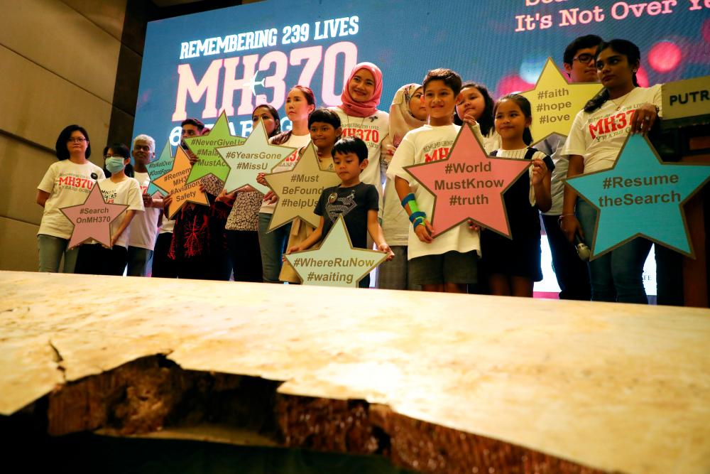 Family members of the victims pose for a group picture with a debris of the missing Malaysia Airlines flight MH370 during its sixth annual remembrance event in Putrajaya, Malaysia, March 7, 2020. — Reuters