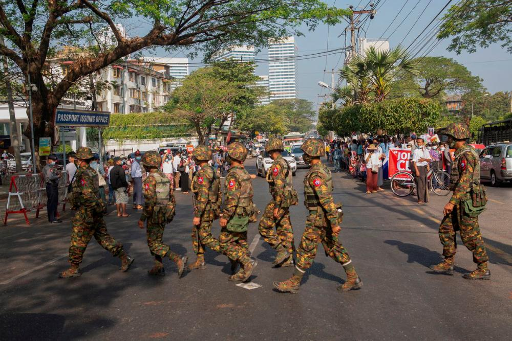 Soldiers cross a street as people gather to protest against the military coup, in Yangon, Myanmar, February 15, 2021. — Reuters/Stringer