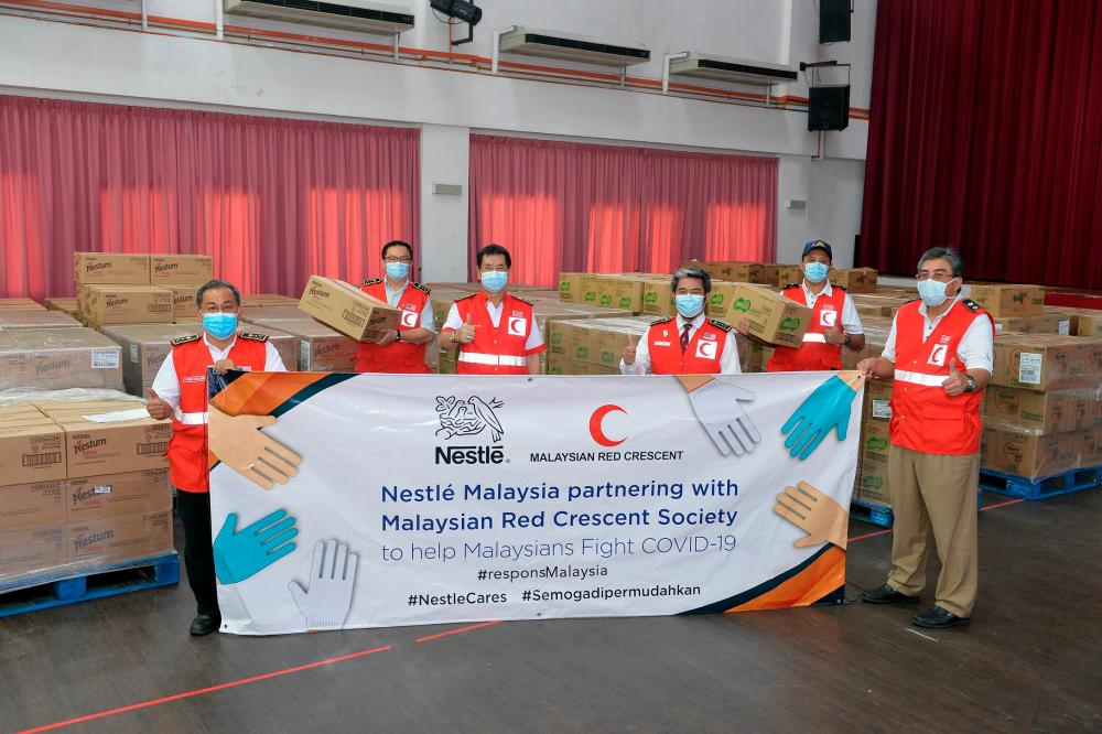 Representatives from the Malaysian Red Crescent Society receiving cash and product donations from Nestlé Malaysia for immediate COVID-19 pandemic relief efforts.