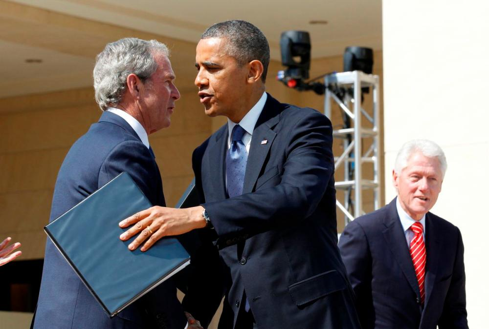 File Photo: U.S. President Barack Obama embraces former President George W. Bush following remarks at the dedication ceremony of the George W. Bush Presidential Center in Dallas, April 25, 2013. Former president Bill Clinton is pictured at right. REUTERSpix