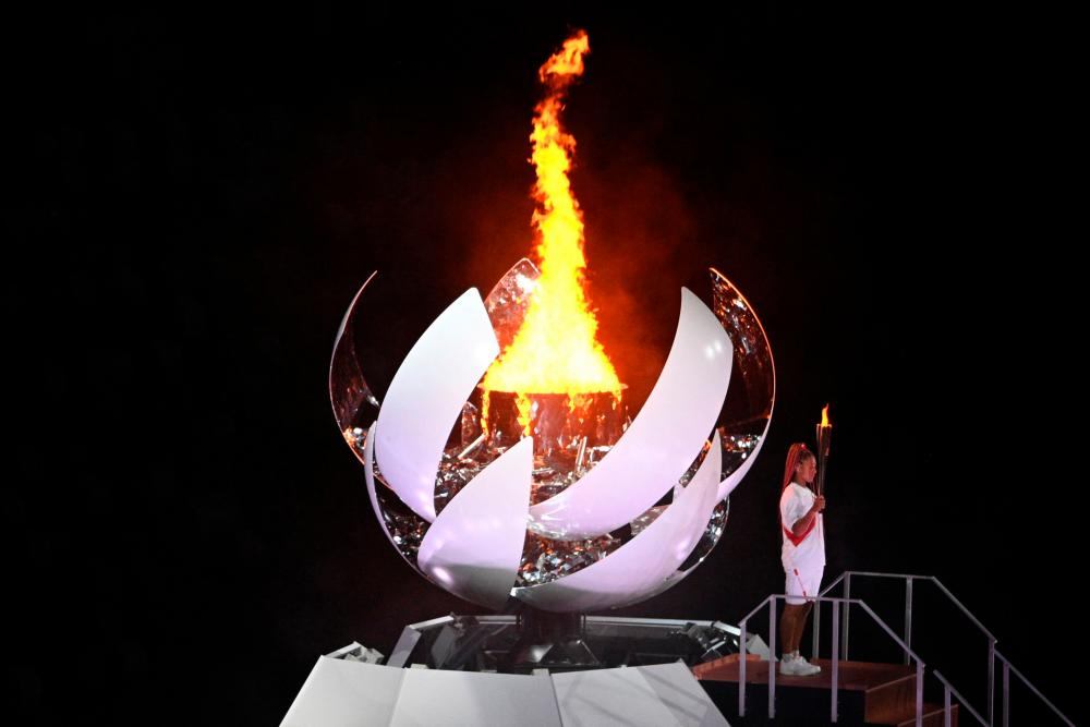 Japan's tennis player Naomi Osaka holds the Olympic torch after lighting the Olympic flame in the Olympic Stadium during the opening ceremony of the Tokyo 2020 Olympic Games, in Tokyo, on July 23, 2021. AFPpix