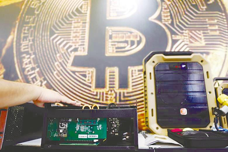 A cryptocurrency mining computer is seen in front of a bitcoin logo. Bitcoin hit its peak of over US$20,000 in late 2017, followed by a plunge in early 2018 to a low of US$3,339. – REUTERSPIX