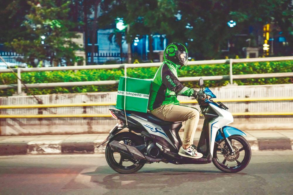 A Gojek rider delivering a Tokopedia package to a customer in Jakarta. – AFPPIX/GoTo Group