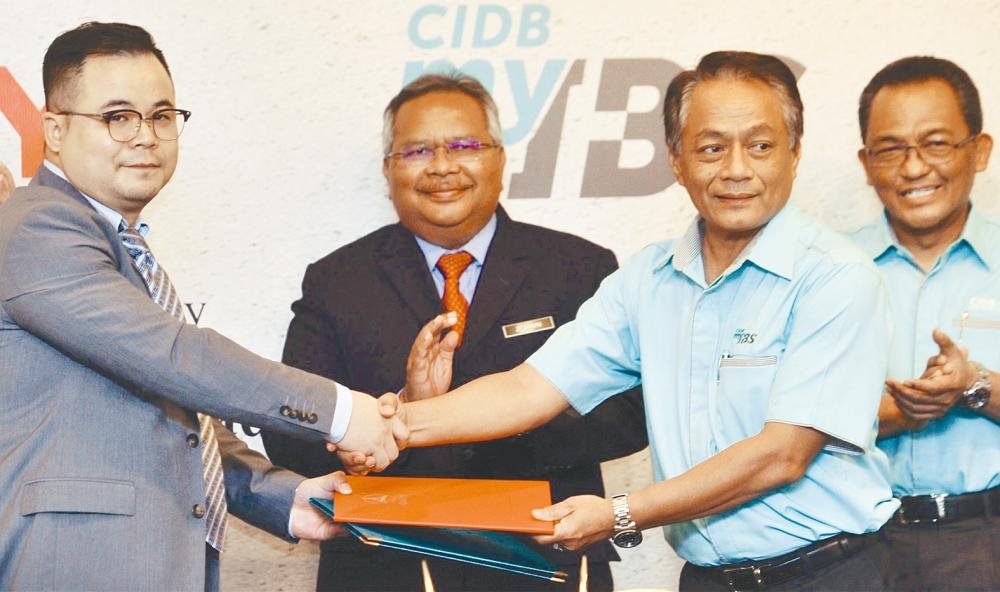Sany managing director Wang Zhenyi (far left) exchanging documents with CIDB IBS deputy chairman Datuk Ir Elias Ismail during the MoU signing ceremony yesterday. - Zulkifli Ersal/THESUN