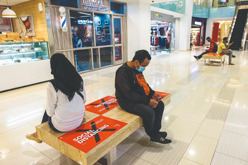 People sit on benches with sections marked off for social distancing at a mall in Surabaya on Monday. Panellists at the CARI roundtable say Asean governments need to help SME address cash flow problems directly by providing loan support to keep them afloat until demand goes back to normal. – AFPPIX