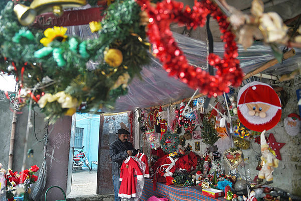 In this picture taken on Dec 12, 2018, Christmas decoration seller Amjab Burgkat tidies his shop in 100 Quarters Colony, one of Islamabad's impoverished Christian ghettos. — AFP