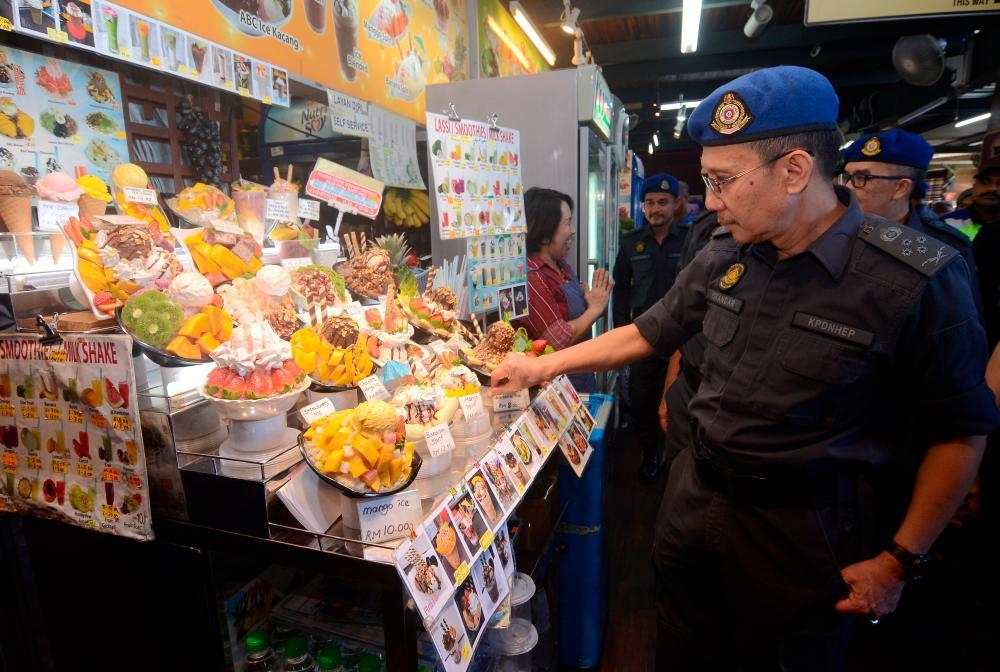 The Domestic Trade and Consumer Affairs Ministry's enforcement director, Datuk Iskandar Halim Sulaiman, inspects a stall during a Price Compliance Programme (Ops Indah) at Bukit Bendera, on Jan 5, 2019. — Bernama