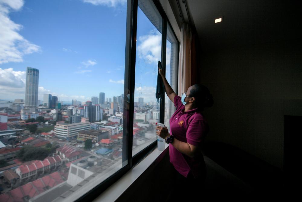 A hotel employee preparing for guests -Bernama
