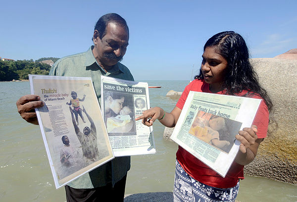 A. Suppiah, 70 shows news pages about his daughter S. Thulasi, 15 (right) the Tsunami's miracle baby, at Batu Ferringhi today. — Bernama