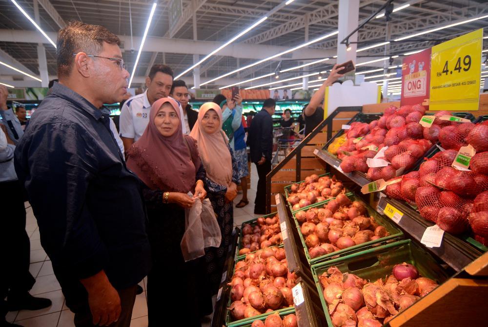 Domestic Trade and Consumer Affairs Minister Datuk Seri Saifuddin Nasution Ismail (L) reviews onion prices after a press conference at Tesco Seberang Jaya yesterday. - Bernama