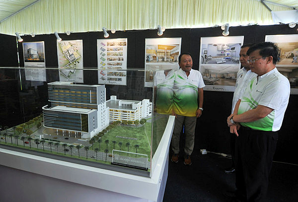 Penang Chief Minister Chow Kon Yeow (R) views the design of Island Hospital's expansion at the hospital's groundbreaking ceremony on Dec 2, 2018. — Bernama
