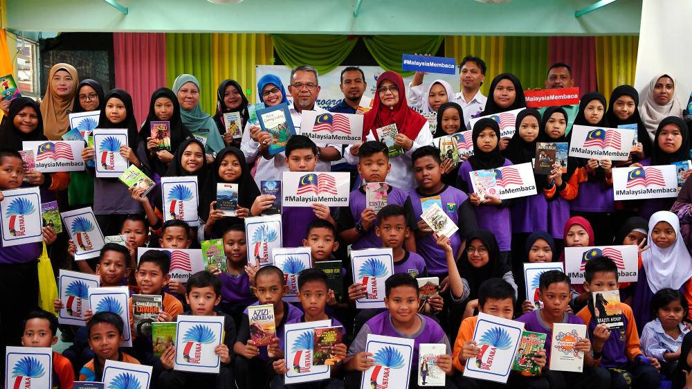 Chief Librarian at the Resource Centre of the Communications and Multimedia Ministry, Hashimah Mohd Yusof (back eight, right) and SK Sungai Lembing headmaster Mohd Shari Muda with students in conjunction with the 'Kasih: Books4U' programme at SK Sungai Lembing on Oct 26, 2019. - Bernama