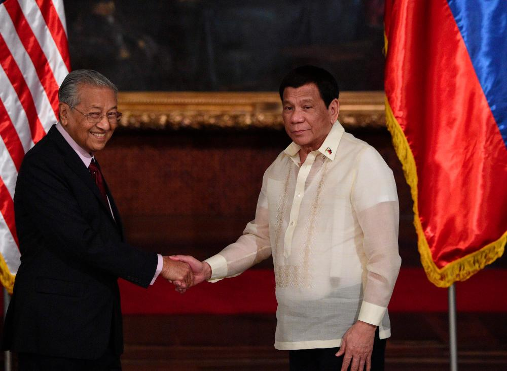 Philippines' President Rodrigo Duterte (R) shakes hands with Malaysia's Minister Mahathir Mohamad after reading their joint statements at the Malacanang Palace in Manila on March 7, 2019. — AFP