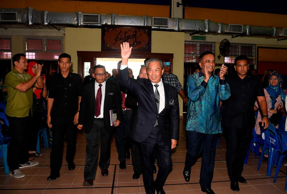 Prime Minister Tan Sri Muhyiddin Yassin waves to students, parents and teachers during a surprise visit to Sekolah Sultan Alam Shah to congratulate students who had excelled in SPM 2019. - Bernama