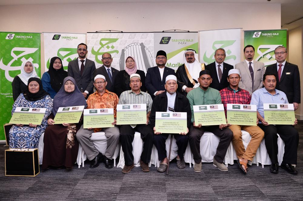 Minister in the Prime Minister's Department Datuk Seri Dr Mujahid Yusof Rawa (5th from R), Saudi Arabia's Ambassador to Malaysia, Datuk Dr Mahmoud Hussein Saeed Qattan (4th from R) and Deputy Minister in the Prime Minister's Department Fuziah Salleh (5th from L) have their picture taken with the benefit recipients today. - Bernama