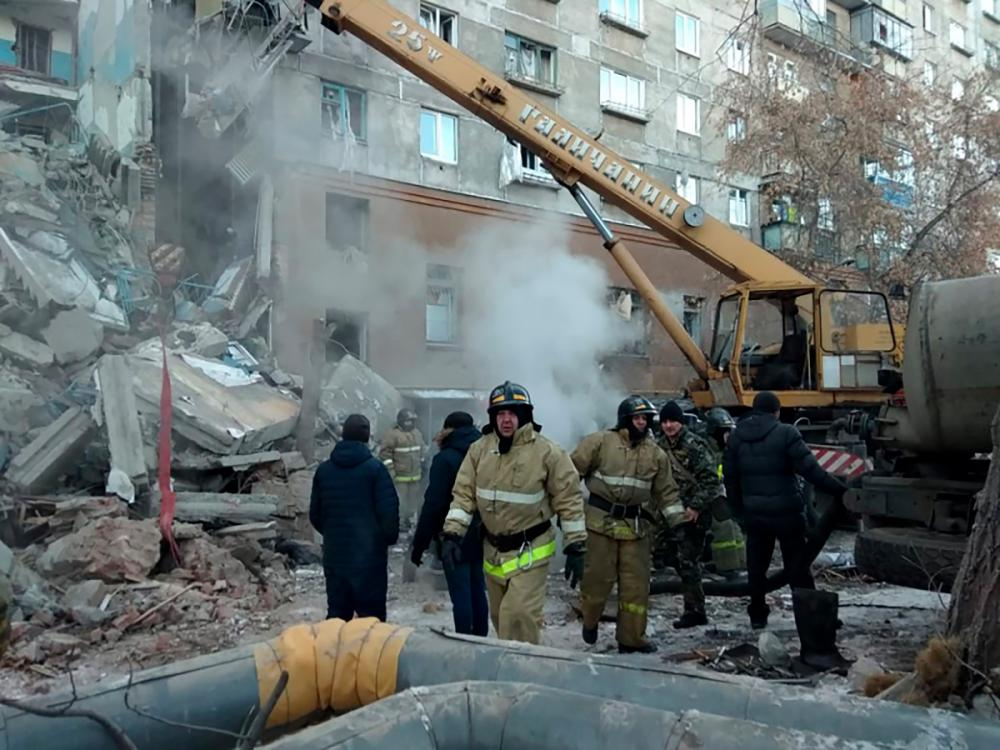 This handout picture released by The Russian Emergency Situations Ministry on Dec 31, 2018, shows emergency officers as they gather after a gas explosion rocked a residential building in Russia's Urals city of Magnitogorsk. — AFP