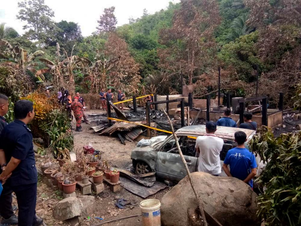 Officers from the Fire and Rescue Department examine the site where five members of a family perished in a fire at a house in Kampung Menara Pamilaan, Tenom, on Dec 31, 2019. — Bernama