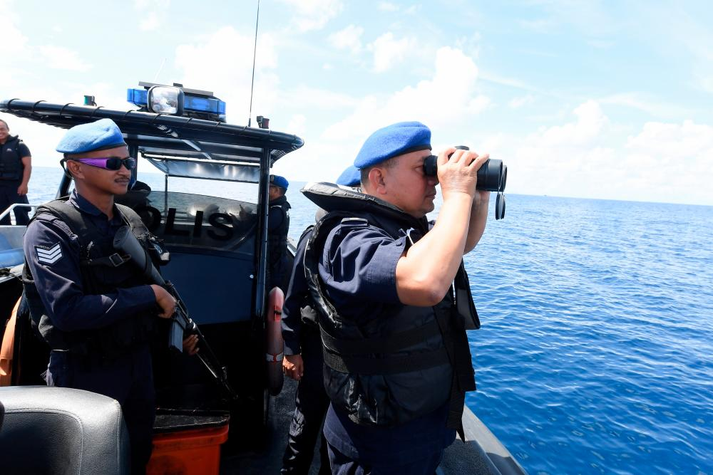 Sabah Marine Police commander Asst Comm Mohamad Pajeri Ali (R) uses a binoculars aboard the boat which is part of the earch and rescue (SAR) for six individuals including two children who were feared drowned after their boat sank in the waters of Merabung, Tungku. — Bernama