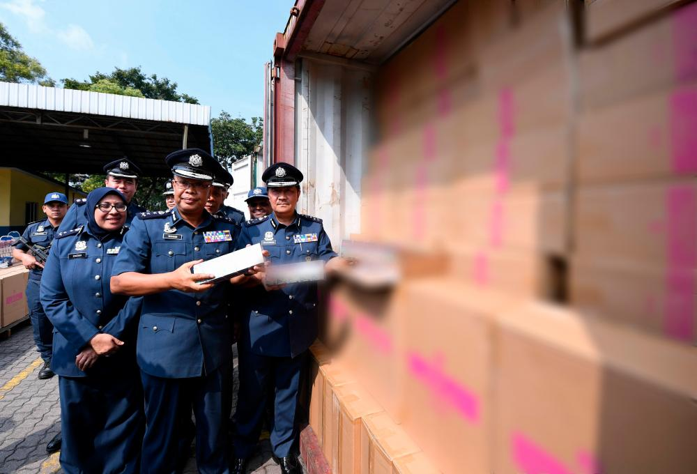 Central Zone Customs assistant director-general Datuk Zulkarnain Mohamed Yusuf (R) shows off some of the seized cigarettes during a press conference in Port Klang today. - Bernama