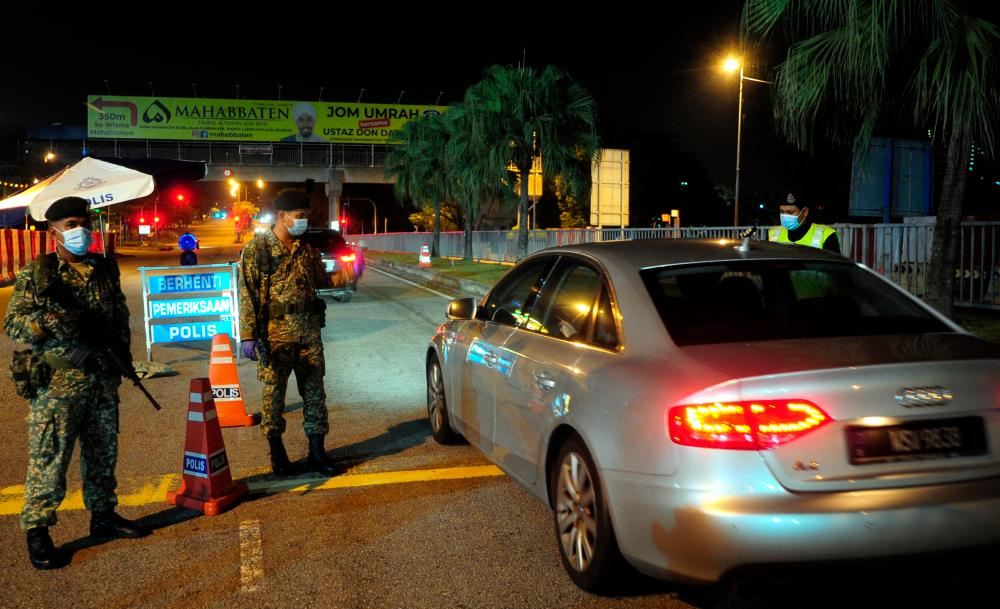 Officers from the Malaysian Armed Forces, during a road block as part of the enforcement of the Movement Control Order (MCO), in Sekysen 7, Shah Alam, on April 1, 2020. — Bernama