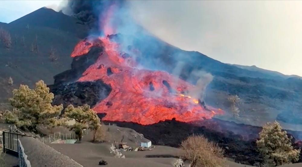 This image grab taken from a video released by the Spanish Geological and Mining Institute (IGME-CSIC) shows one of the lava streams flowing and carrying massive block stones after a cone collapsed in the north side of the Cumbre Vieja volcano, in the Canary Island of La Palma, on October 11, 2021. AFPpix