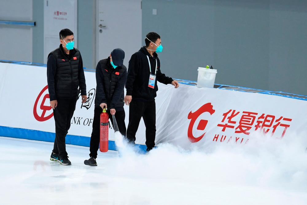 Staff members spray the track during the Speed Skating China Open, part of the 2022 Beijing Winter Olympic Games test event, at the National Speed Skating Oval in Beijing on October 10, 2021. AFPpix
