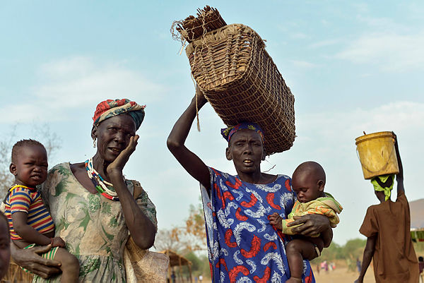Women carrying children at a market in Udier town, South Sudan — AFP