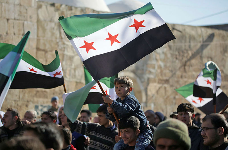 Syrians brandish opposition flags during a demonstration in support of neighbouring Turkey in the town of Bizaa, north of Aleppo on Dec 21, 2018. — AFP