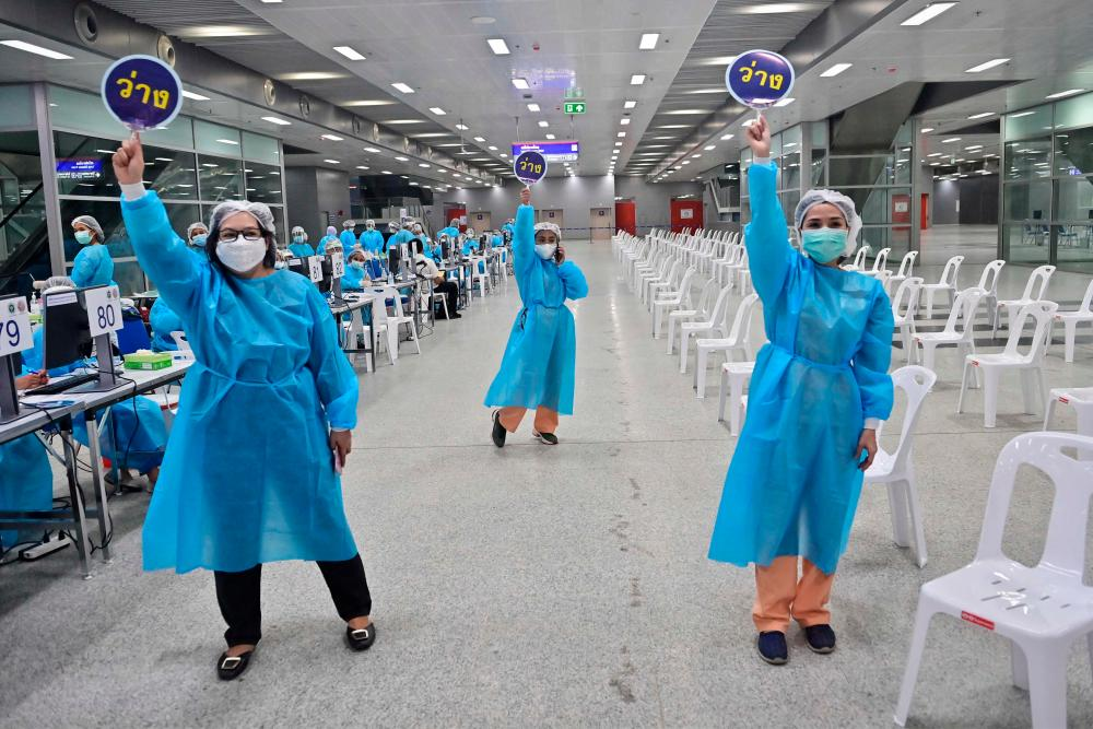 Health workers call for people to receive doses of the Covid-19 coronavirus CoronaVac vaccine at Bang Sue Central Station in Bangkok on May 24, 2021. AFPpix