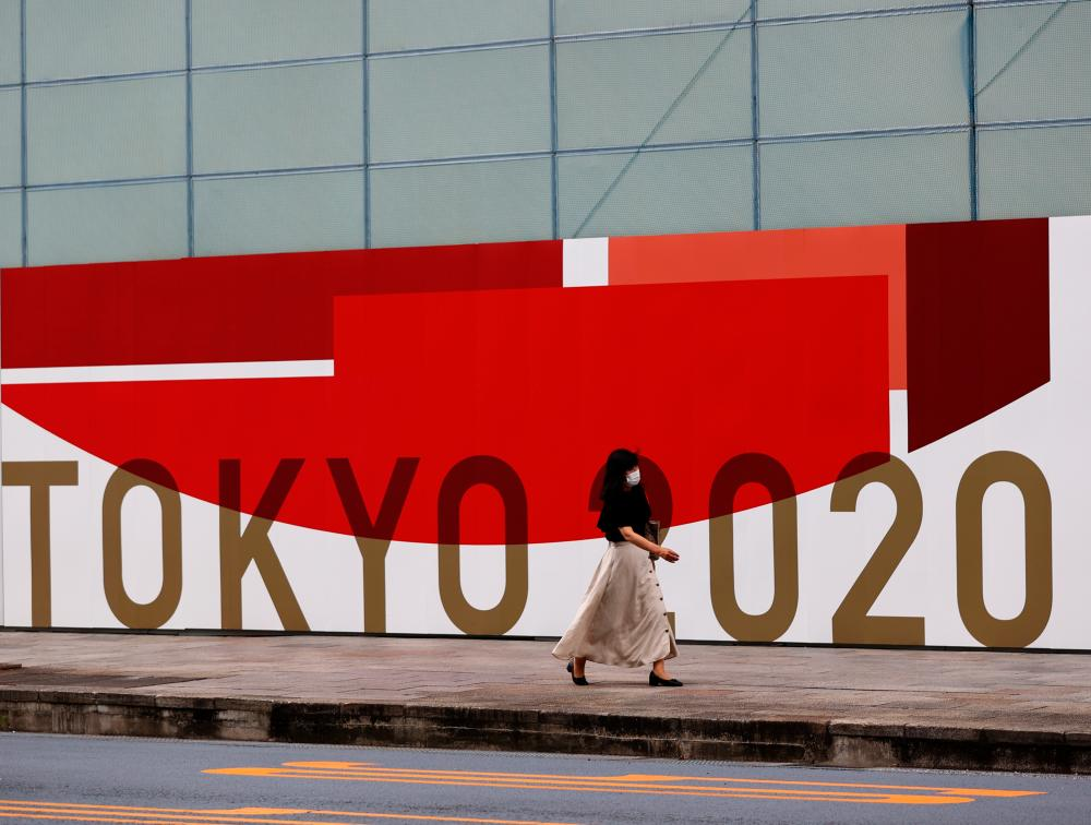 A woman, wearing a protective mask against Covid-19, walks past a wall bearing logo of Tokyo 2020 Olympic Games in Tokyo, Japan, July 29, 2021. — Reuters