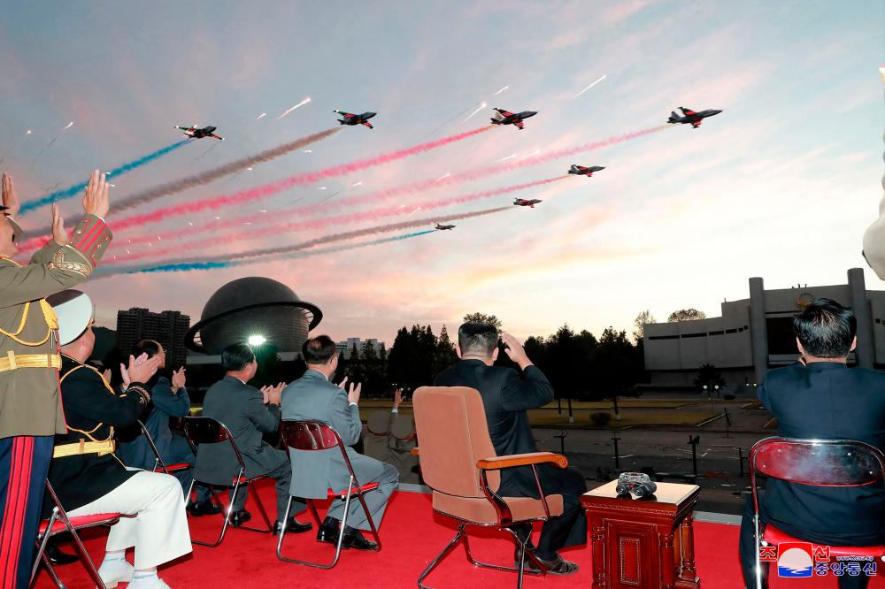 """This picture taken on October 11, 2021 and released from North Korea's official Korean Central News Agency (KCNA) on October 12 shows North Korean leader Kim Jong Un (2nd-R) watching a demonstration flight during the opening ceremony of the defence development exhibition """"Self-Defence-2021"""" in Pyongyang. AFPpix"""