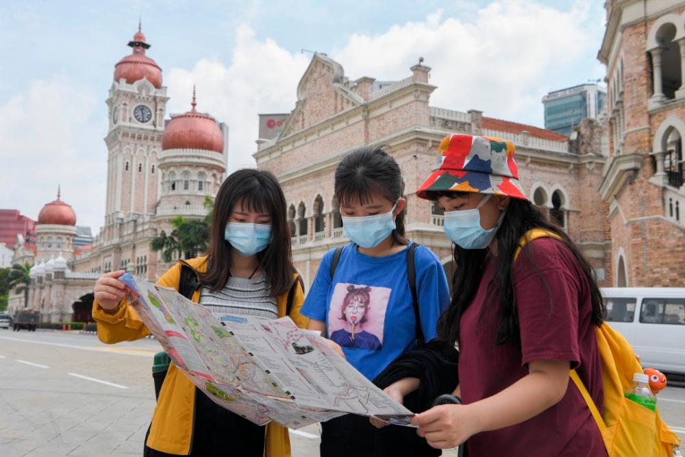 A group of Taiwanese tourists don face masks during their visit to Dataran Merdeka as a safety precaution in light of the Covid-19 outbreak. — Bernama