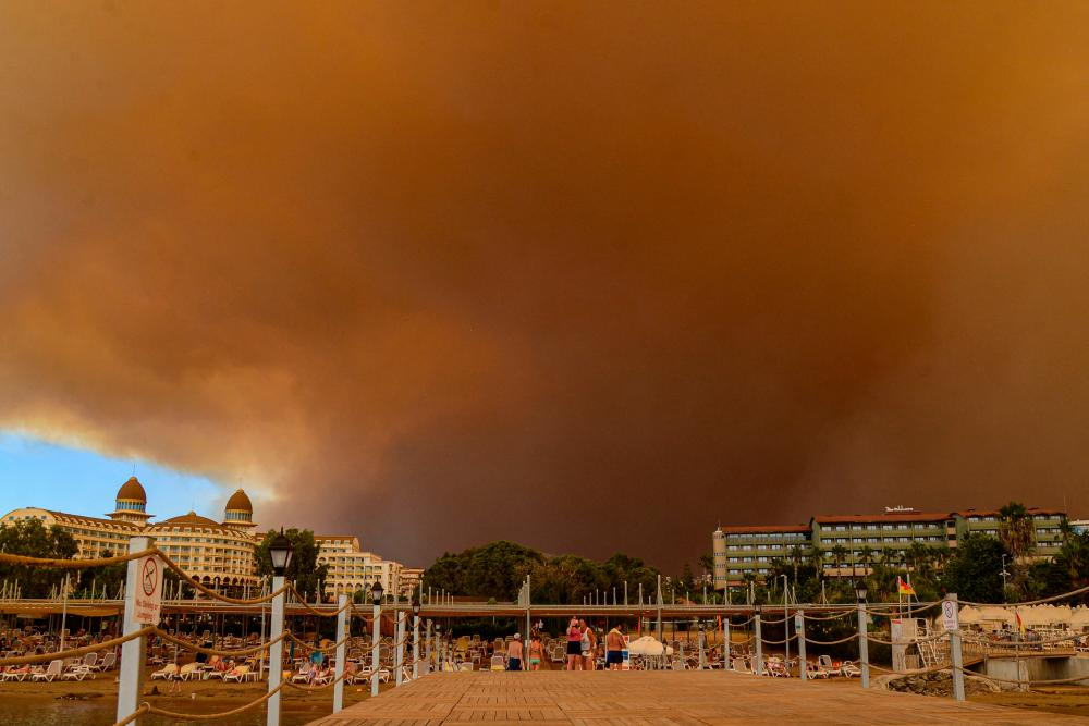 Dark smoke drifts over a hotel complex during a massive forest fire which engulfed a Mediterranean resort region on Turkey's southern coast near the town of Manavgat, on July 29, 2021. At least three people were reported dead on July 29, 2021 and more than 100 injured as firefighters battled blazes engulfing a Mediterranean resort region on Turkey's southern coast. Officials also launched an investigation into suspicions that the fires that broke out Wednesday in four locations to the east of the tourist hotspot Antalya were the result of arson. -AFP