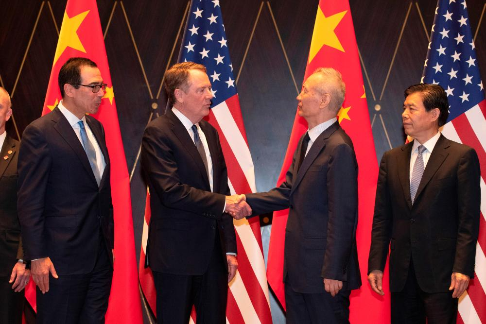 US Trade Representative Robert Lighthizer shakes hands with Chinese Vice Premier Liu He as US Treasury Secretary Steven Mnuchin and China's Commerce Minister Zhong Shan look on during a family photo at the Xijiao Conference Center in Shanghai, China, July 31, 2019. - Reuters