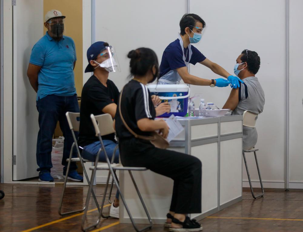 People receive a dose of the Covid-19 vaccine during Selangor Vaccination Programme (Selvax) at Dewan Seberguna Taman Eng Ann Klang. — Asyraf Rasid /THESUN