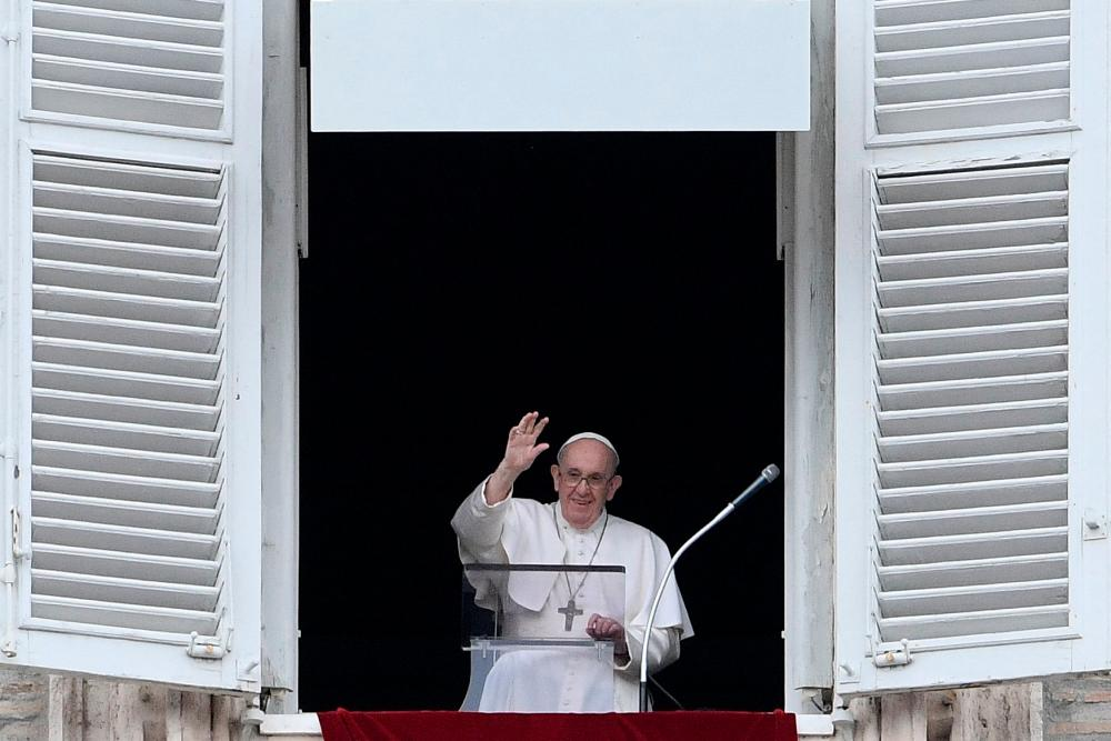 Pope Francis waves as he delivers the Sunday Angelus prayer from the window of his study overlooking St.Peter's Square at the Vatican on July 25, 2021. -AFP