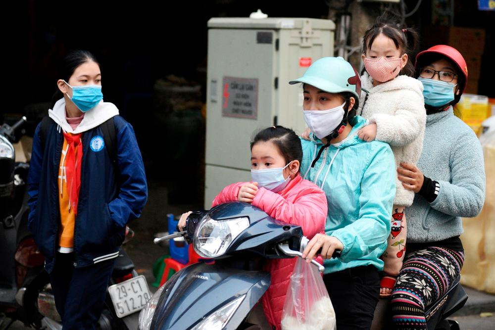 FILE PHOTO: A family wears protective masks as they ride a motorbike in the street amid the coronavirus disease (Covid-19) outbreak in Hanoi, Vietnam, January 29, 2021. — Reuters