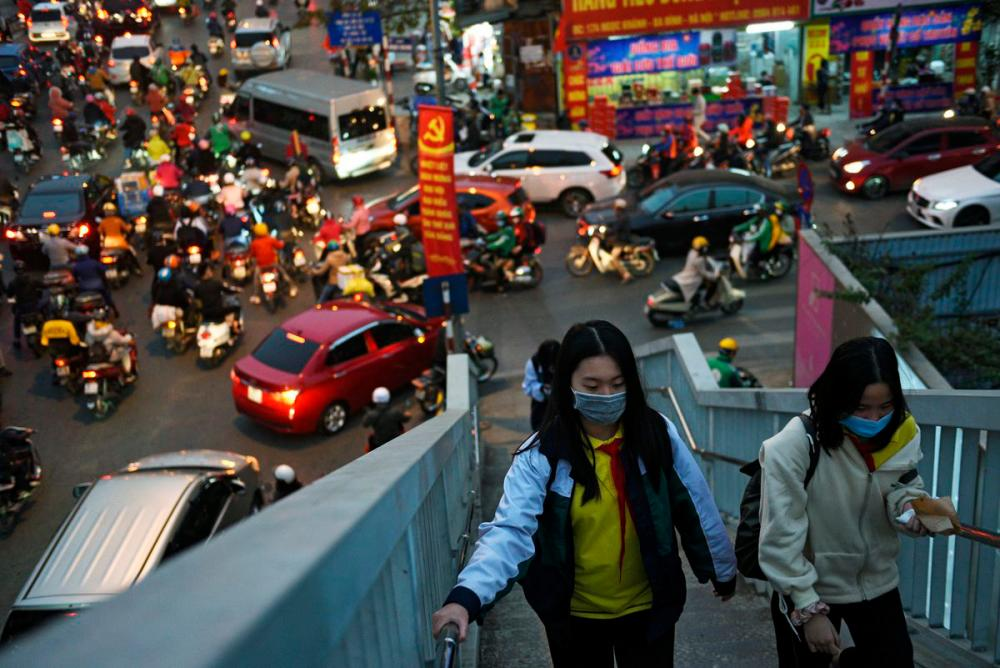 Girls walk in a overpass as they wear protective masks in the street amid the coronavirus disease (Covid-19) outbreak in Hanoi, Vietnam, January 29, 2021. — Reuters
