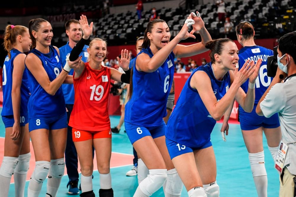 Russia's players celebrate their victory in the women's preliminary round pool B volleyball match between USA and Russia during the Tokyo 2020 Olympic Games at Ariake Arena in Tokyo on July 31, 2021. -AFP