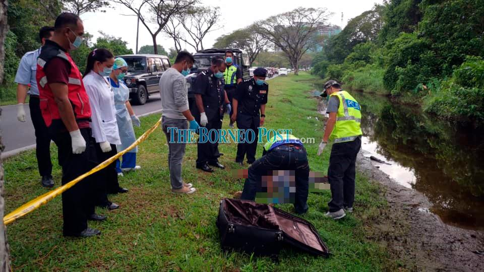 Police personnel examining the body at the scene.