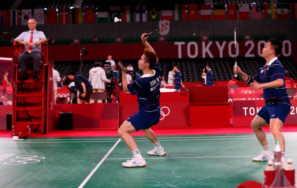 Soh Wooi Yik of Malaysia in action near Aaron Chia of Malaysia during the match against Jason Ho-Shue of Canada and Nyl Yakura of Canada. — Reuters