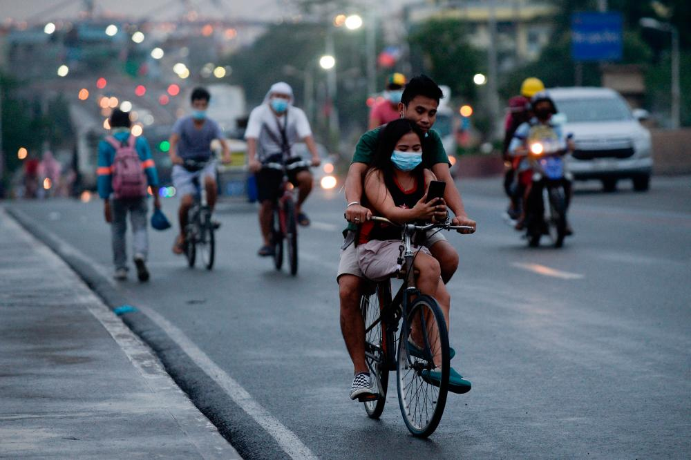 FILE PHOTO: A cyclist carries a passenger wearing a protective face mask, amid the coronavirus disease (Covid-19) pandemic, in Manila, Philippines, June 11, 2021. -Reuters